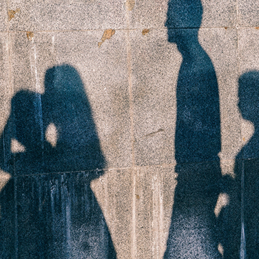 Pictures of four people's shadows on a wall